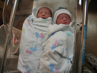 Andrew and Ryan snuggled together in a bassinet. (Andrew's on the left... Ryan on the right...